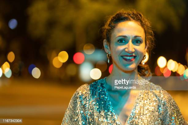 Elegant woman with a silver dress at night