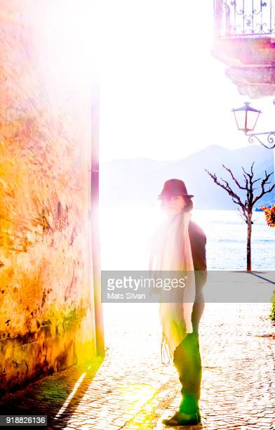elegant woman with hat and scarf standing on an old street with sunlight - kanton tessin stock-fotos und bilder