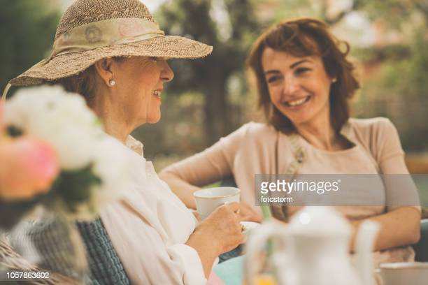 elegant women having tea outdoors - afternoon tea stock pictures, royalty-free photos & images