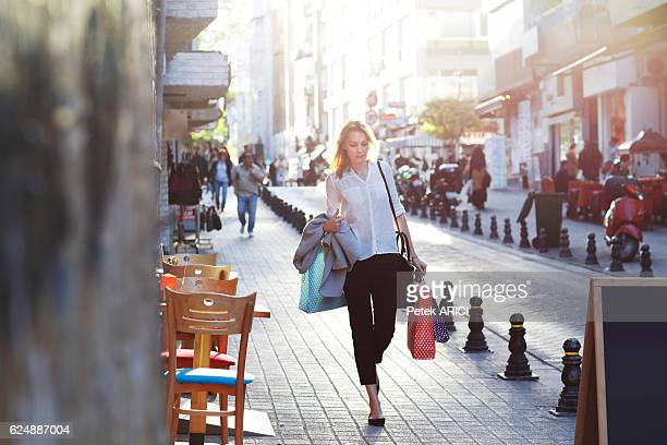 Elegant women walking the crowded city with shopping bags