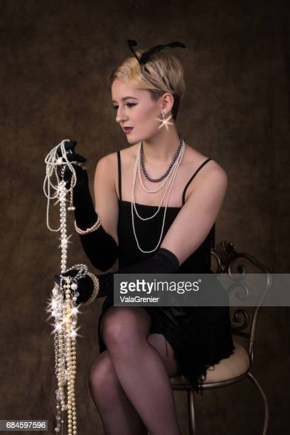 elegant young blonde woman in 1920s era outfit, three quarter length sitting. - flapper stock photos and pictures