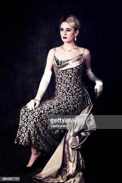Elegante junge blonde Frau in der 1940er Jahre Ära Outfit, sitzen in voller Länge.
