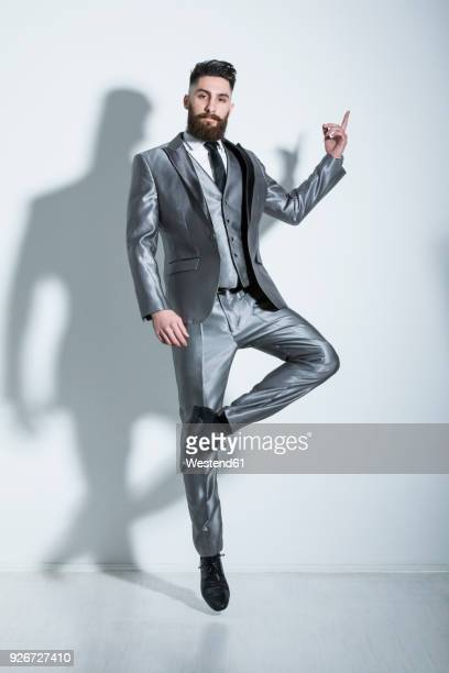 elegant young man jumping and dancing gracefully - double breasted stock pictures, royalty-free photos & images