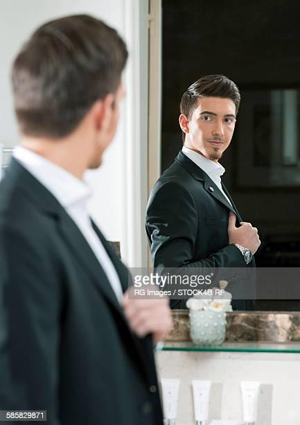 Elegant young man looking in mirror