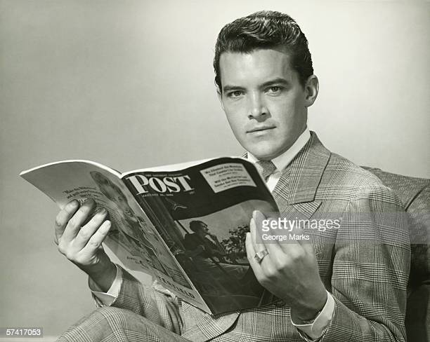 elegant young man reading magazine in studio, (b&w), (portrait) - picture magazine stock pictures, royalty-free photos & images