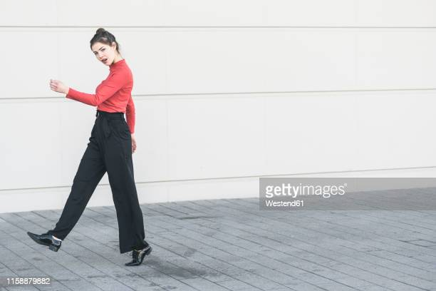 elegant young walking along a wall - black trousers stock pictures, royalty-free photos & images