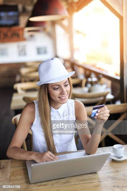 Elegant young woman drinking coffee and using credit card