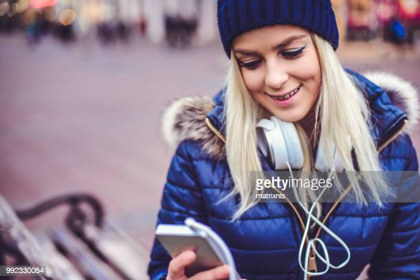 elegant young woman listens to her music in the city - down blouse stock pictures, royalty-free photos & images