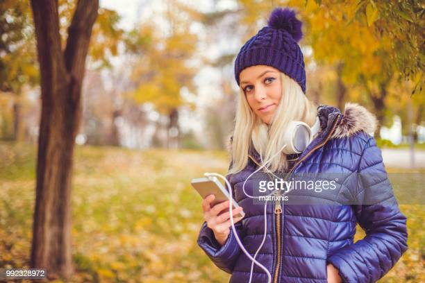 elegant young woman listens to her music in the park - down blouse stock pictures, royalty-free photos & images
