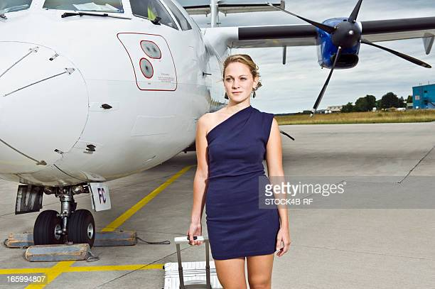elegant young woman on the runway of an airport - asymmetric dress stock pictures, royalty-free photos & images