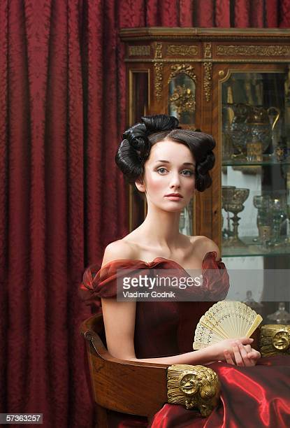 elegant young woman seated in red ball gown and holding fan - throne stock pictures, royalty-free photos & images