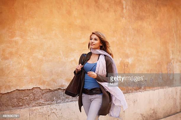 Elegant young woman strolling down street