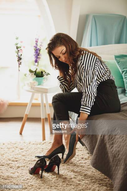 elegant young woman trying on high heels while getting ready - women trying on shoes stock pictures, royalty-free photos & images