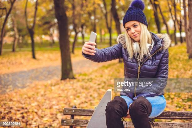elegant young woman uses smartphone  in the park, selfie time. - down blouse stock pictures, royalty-free photos & images