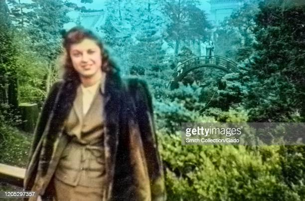 Elegant young woman wearing a fur coat and standing in front of the iconic barrel bridge in the Hagiwara Japanese Tea Garden in Golden Gate Park, San...