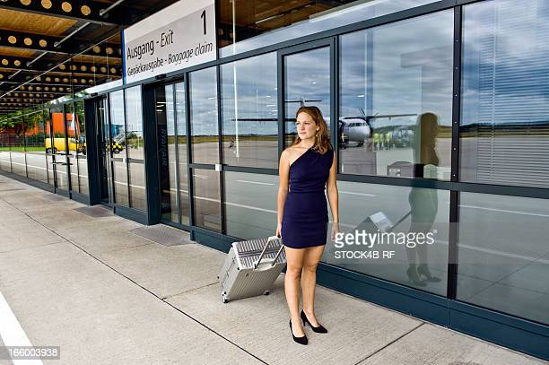 elegant young woman with metal suitcase at the airport - asymmetric dress stock pictures, royalty-free photos & images