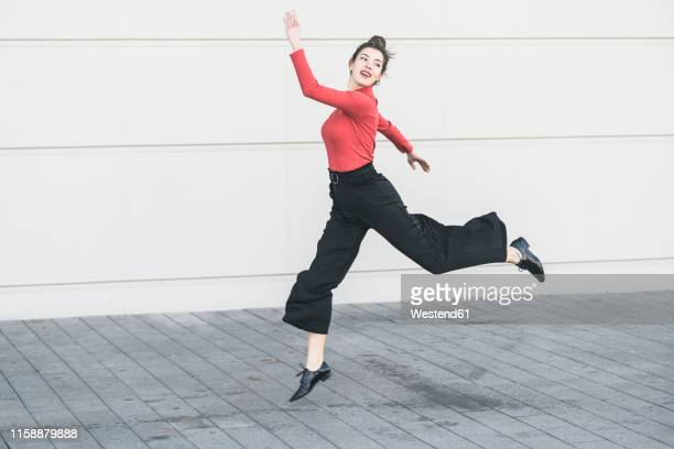 elegant young women jumping in front of a wall - white pants stock pictures, royalty-free photos & images