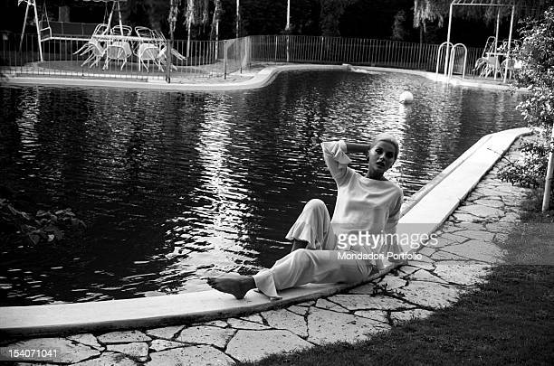Elegantly dressed the Italian actress Virna Lisi born Virna Pieralisi is sat in a sensual pose on the border of the deck level swimming pool of her...