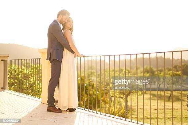 elegantly dressed young couple standing on veranda