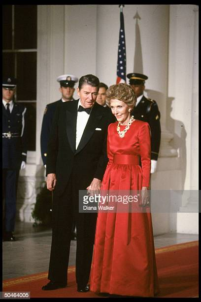 Elegantly garbed Pres Nancy Reagan holding hands poised on red carpet during State Dinner in honor of Brtish PM