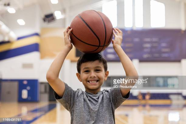 elementary age boy goofs off with basketball for camera - play off stock pictures, royalty-free photos & images