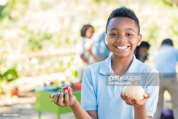 Elementary age boy holding vegetables in school garden