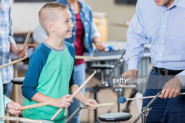 Elementary age boy listens attentively to band teacher