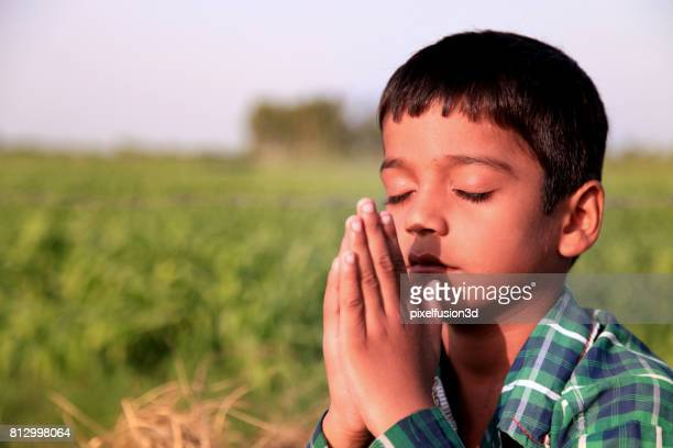 elementary age boy praying to god - praying stock pictures, royalty-free photos & images
