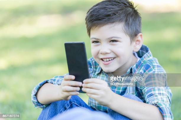 Elementary age boy takes selfie outdoors