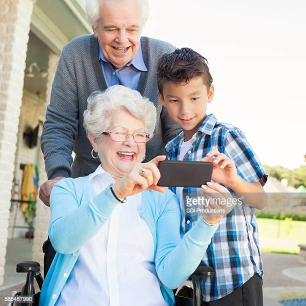 Elementary age boy takes selfie with grandparents