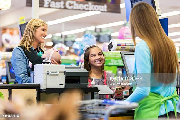 Elementary age customer using cash to pay for supermarket purchases
