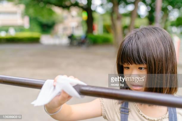遊ぶ前にアルコールウェットワイプで遊具を消毒小学校の女の子 - 消毒用アルコール ストックフォトと画像