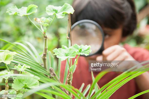 Elementary age girl enjoys discovering nature. Magnifying glass.