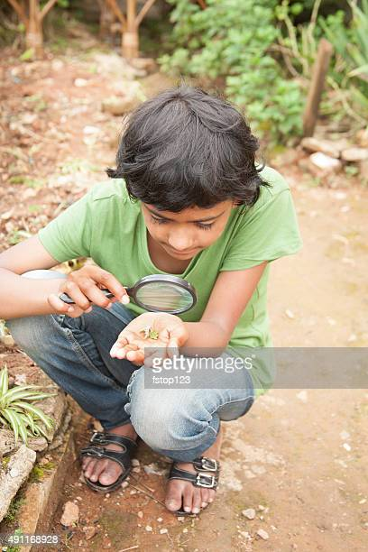Elementary age girl enjoys discovering nature. Magnifying glass. Plant.