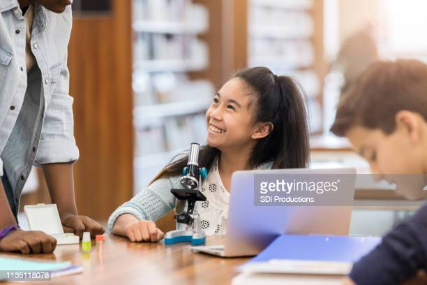 elementary age girl enjoys science help from teacher - science photo library stock pictures, royalty-free photos & images