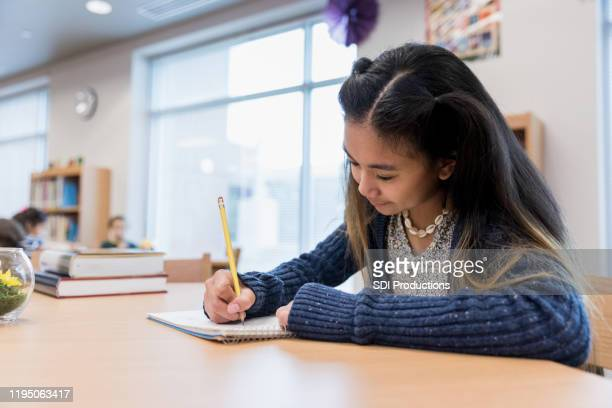 elementary age girl focuses on her homework - junior high student stock pictures, royalty-free photos & images