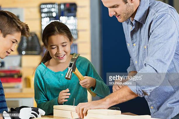 Elementary age girl hammers nail into board