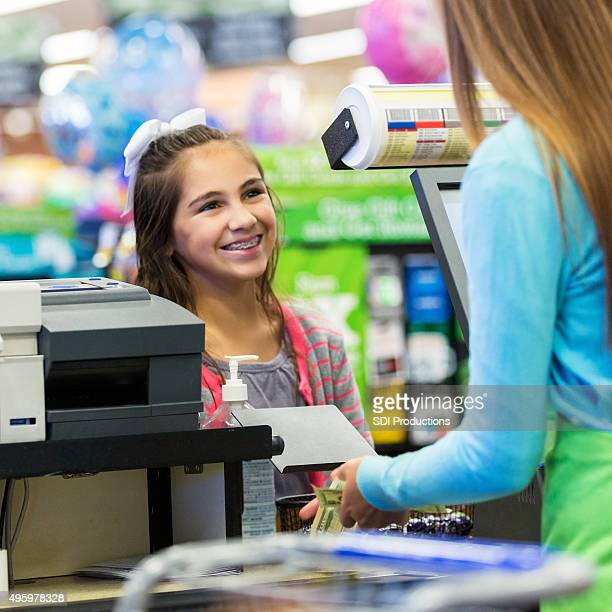 Elementary age girl paying for something at grocery store