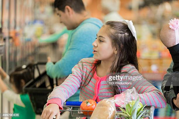Elementary age girl shopping for groceries with mom in supermarket