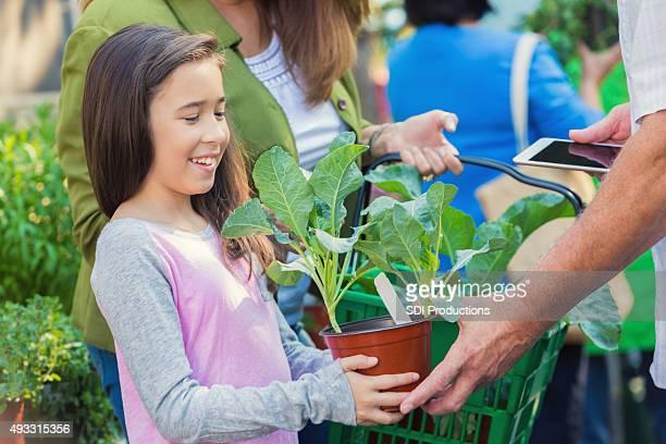 Menina de escola primária de compras para plantas com a família no infantário