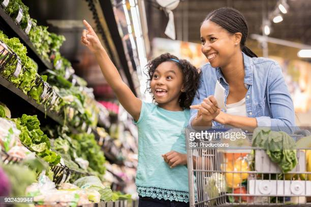 elementary age girl shopping with her beautiful mom - leaf vegetable stock pictures, royalty-free photos & images