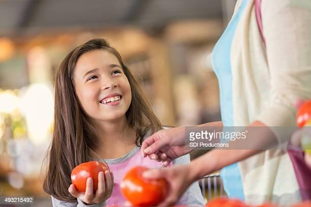 Escola primária menina a sorrir com mãe compras de mercearia,