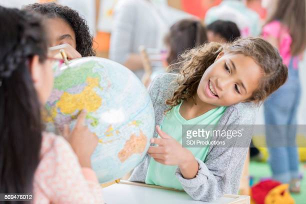 elementary age girl studies globe with friends - southern hemisphere stock photos and pictures