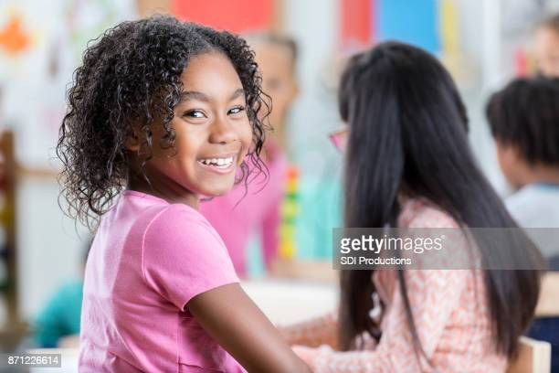 Elementary age girl turns and smiles for camera at school