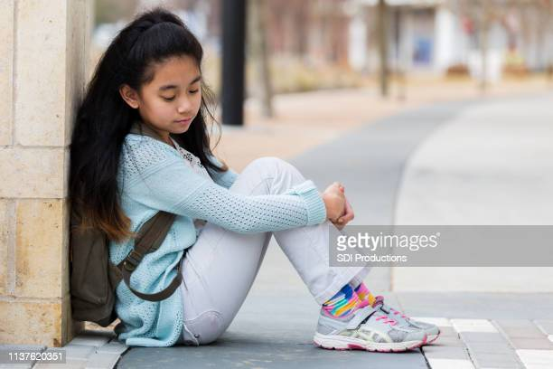 elementary age girl waits for ride outside school - school girl shoes stock pictures, royalty-free photos & images