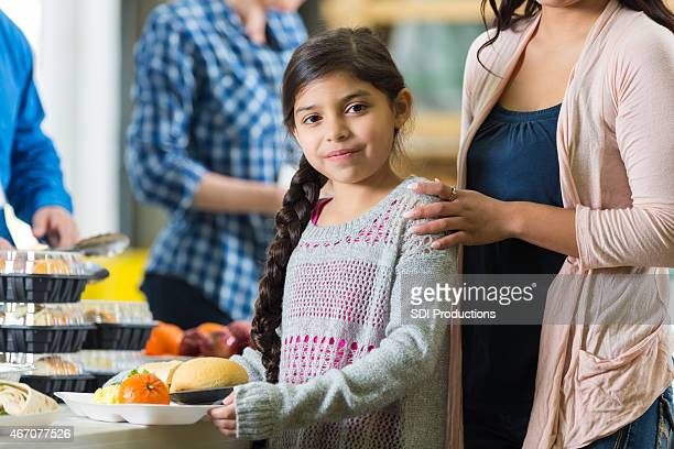 Elementary age Hispanic girl with tray in food bank kitchen