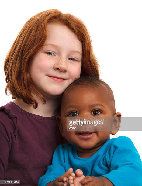 elementary age redhead girl hugging 6month old adopted black sister - black ginger baby stock photos and pictures