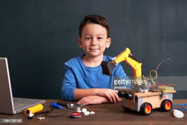 menino de escola elementar idade cria robô - 6 7 anos - fotografias e filmes do acervo