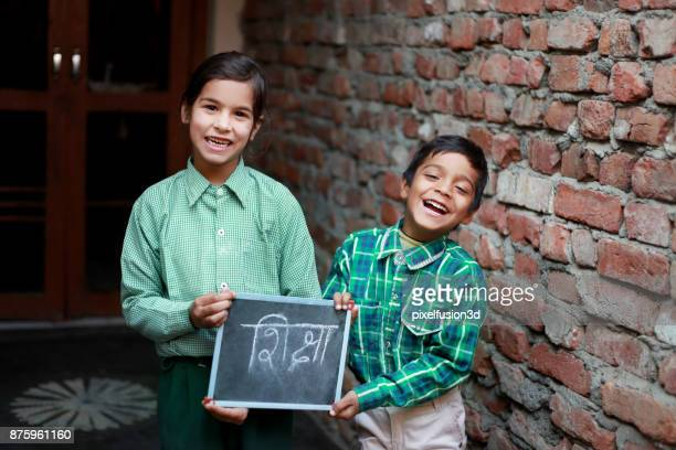 elementary age school child showing chalkboard - haryana stock photos and pictures