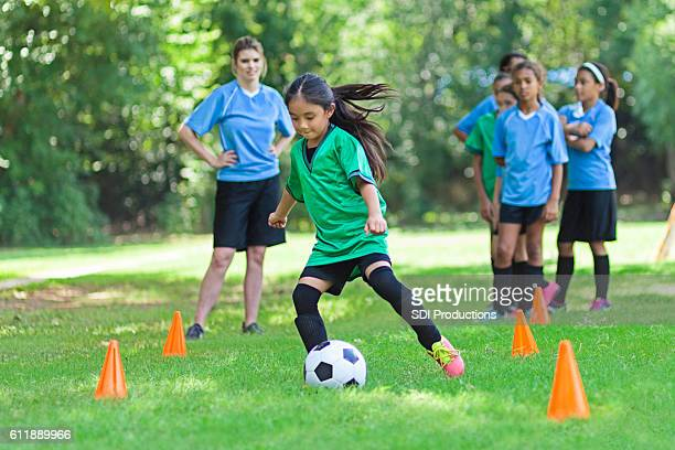 Elementary age soccer athlete kicks ball around cones